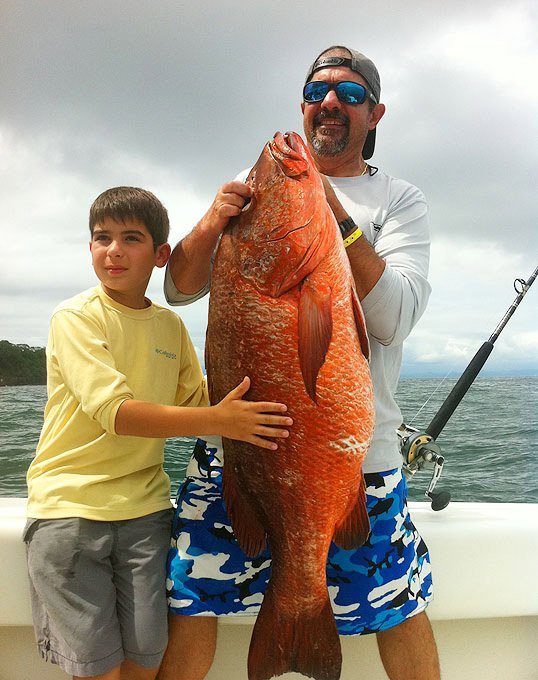 Dad and his son holding a caught fish