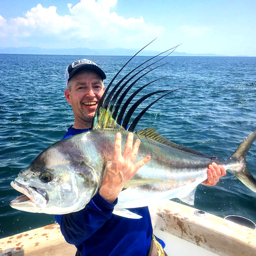 man with a rooster fish on a Costa Rican fishing charter