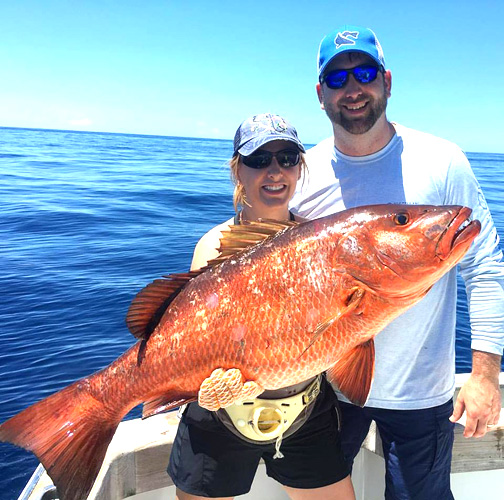 couple with a fish on a Los Suenos fishing charter